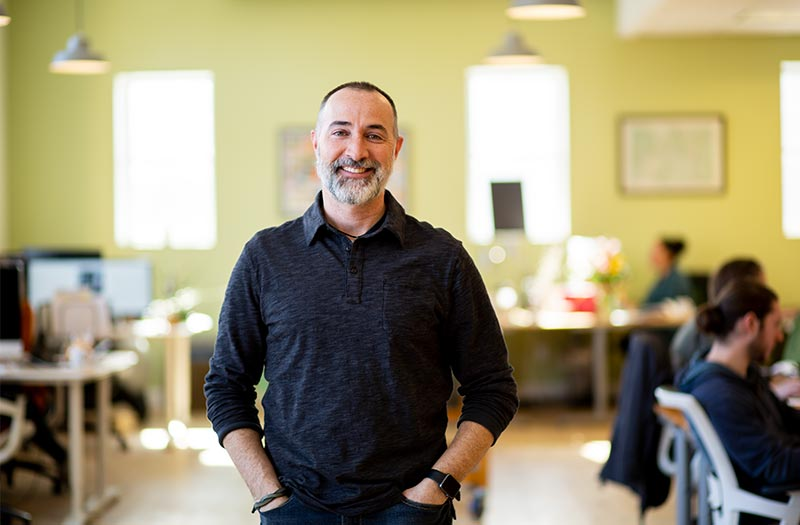 Man in dark shirt posing for photo