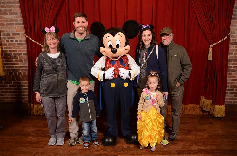 Family posing with Mickey Mouse