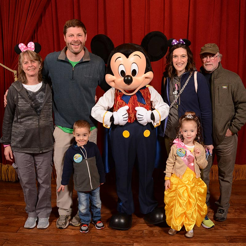 Parent and kids posing with Mickey Mouse