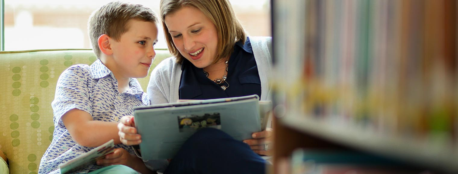 Women reading book to young boy